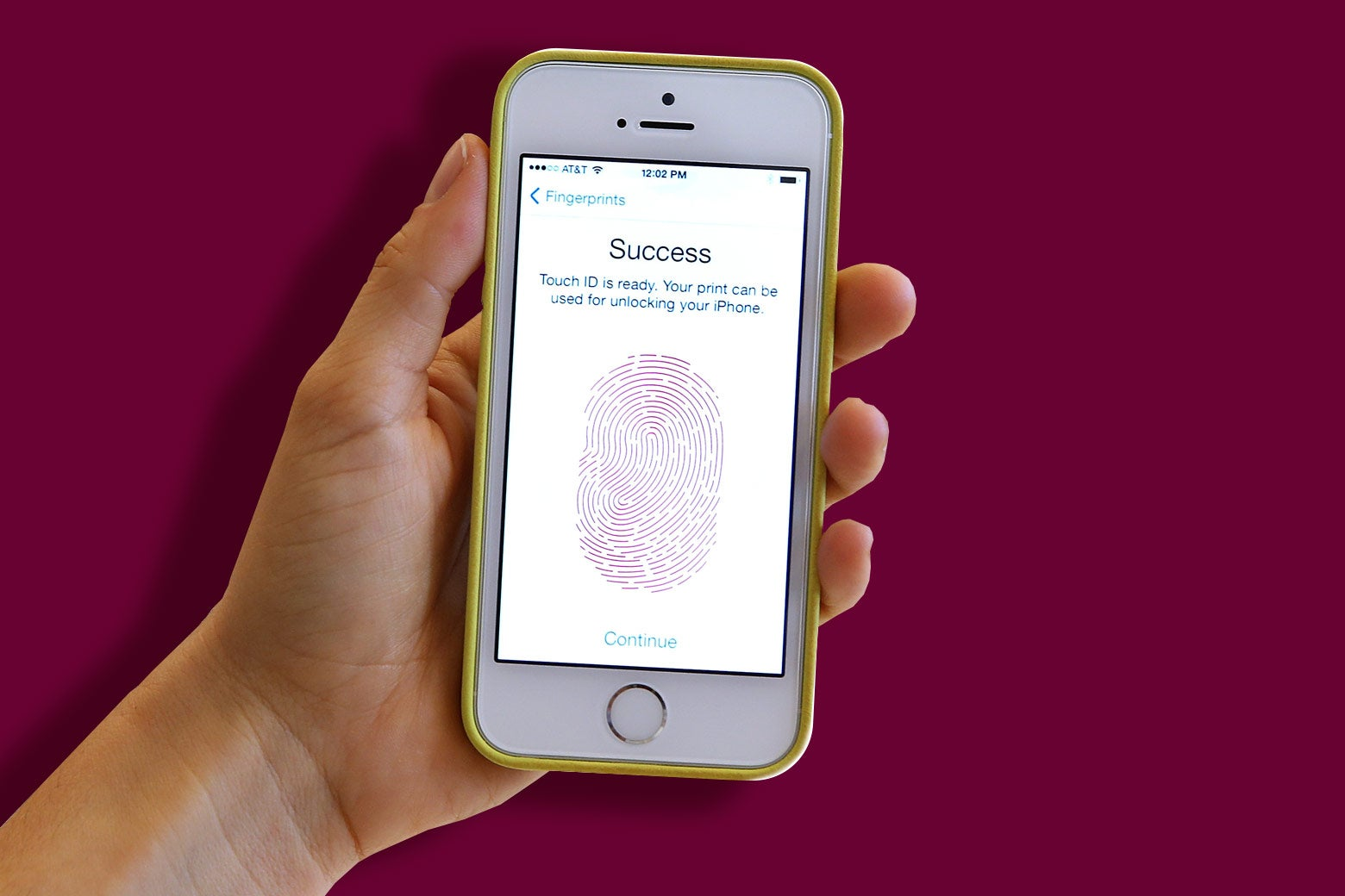 A hand holding an iPhone. The screen shows that the user has just set up Touch ID.