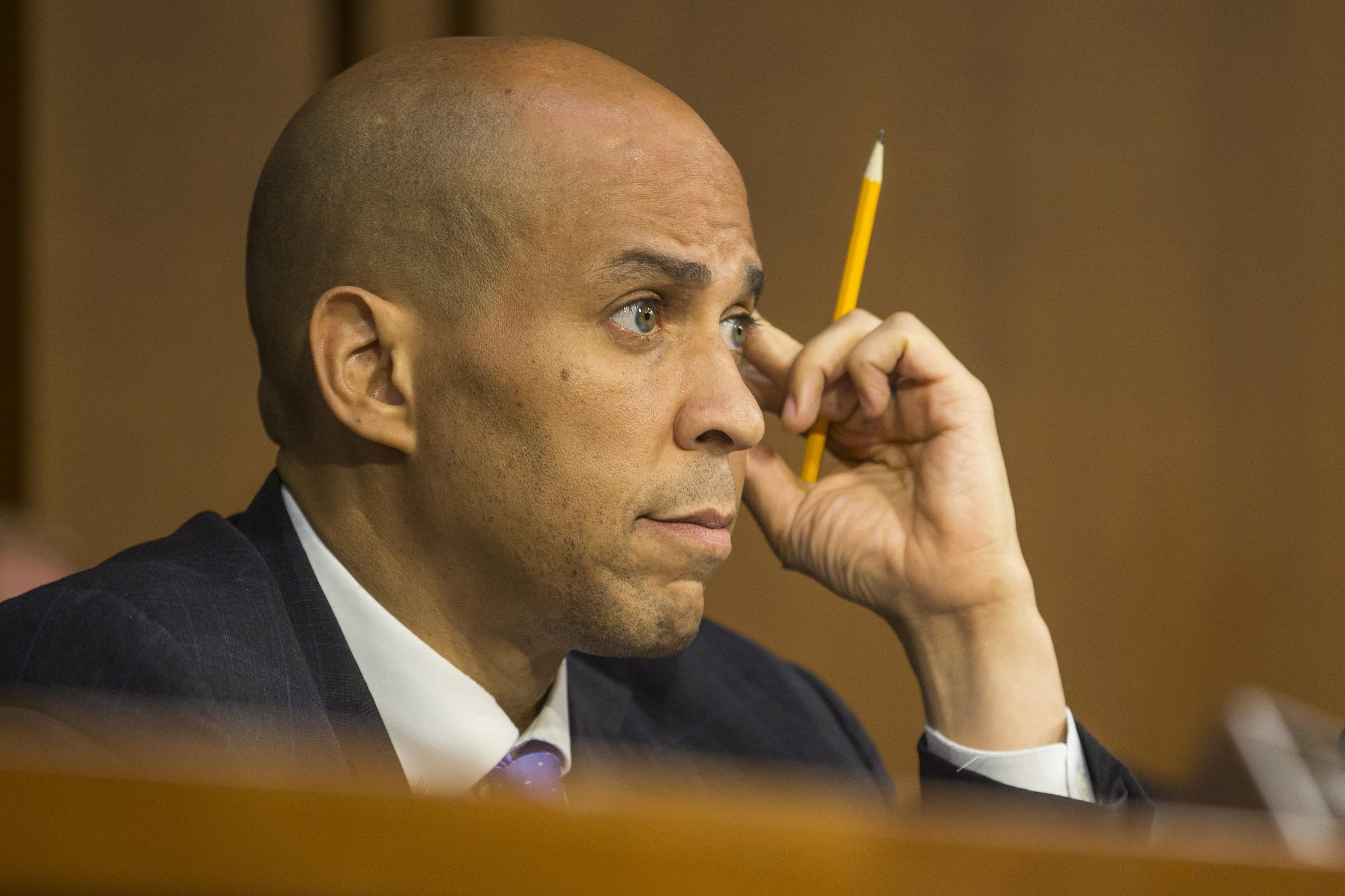 New Jersey Sen. Cory Booker touches his temple while holding a pencil as he listens during the second day of Brett Kavanaugh's confirmation hearing on Wednesday.