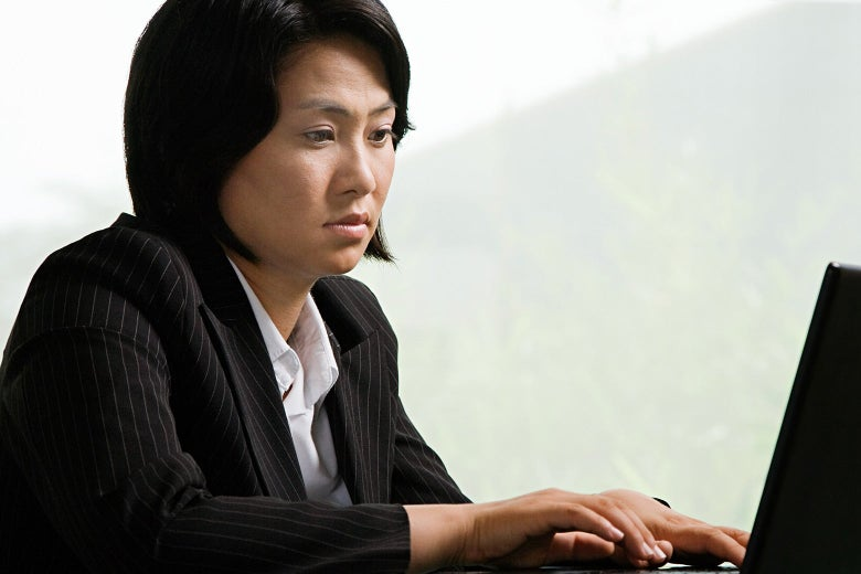 A woman staring at a laptop with glazed eyes.