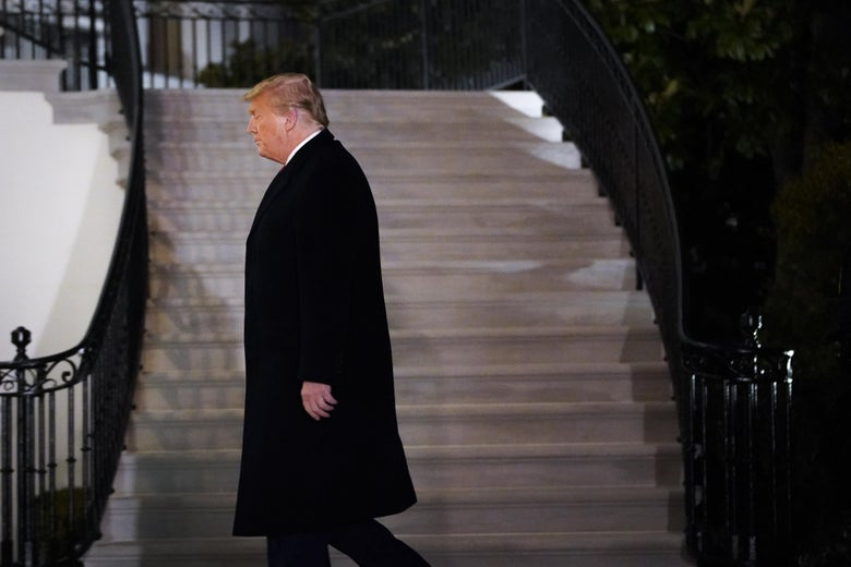 Trump in profile as he walks to the White House residence at night