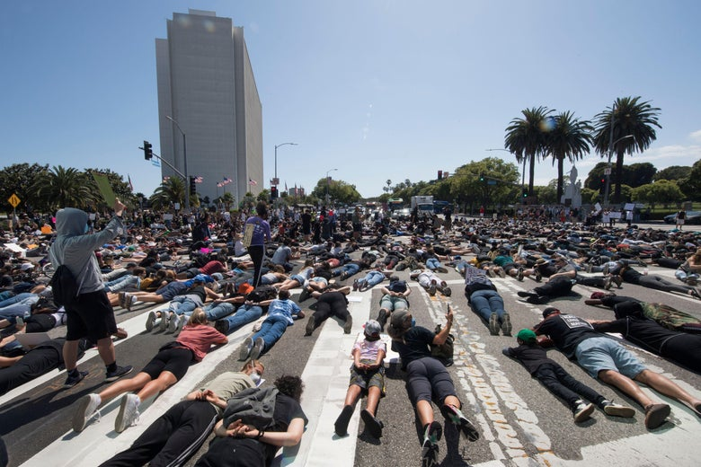 Protesters lie in the street as they block an intersection outside the Federal Building on busy Wilshire Blvd as they demonstrate against the death of George Floyd, in Westwood, California, on June 6, 2020.