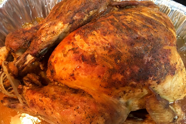 A golden-brown turkey in a foil roasting pan.