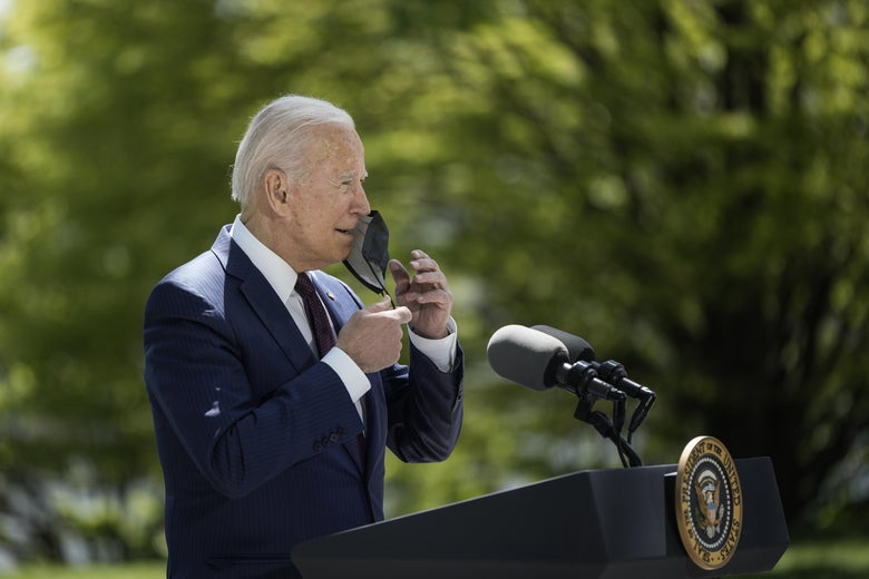 Joe Biden, seen from the side, reaches up and removes a mask from his face as he stands outdoors wearing a navy suit at a presidential lectern with green trees in the background.