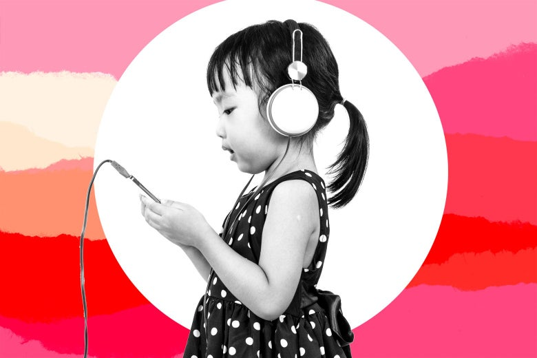 A little girl watching a tablet with headphones on.