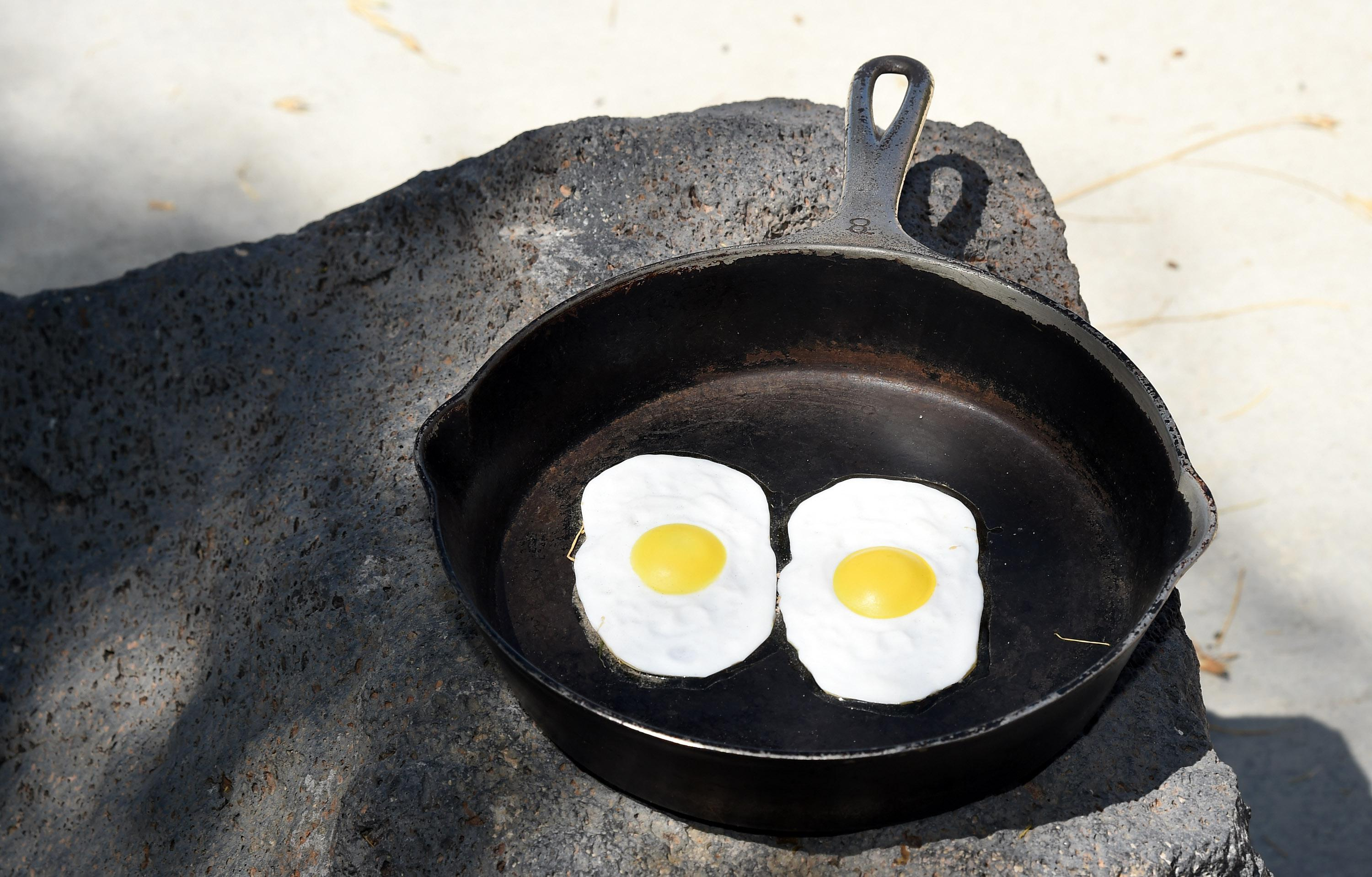 Fake eggs in a frying pan are displayed near a 134-foot-high electronic sign that gives the temperature on July 23, 2014 in Baker, California.