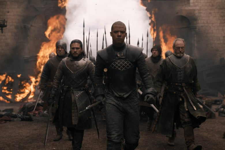 Jon Snow and friends striding through a burnt-down wall.