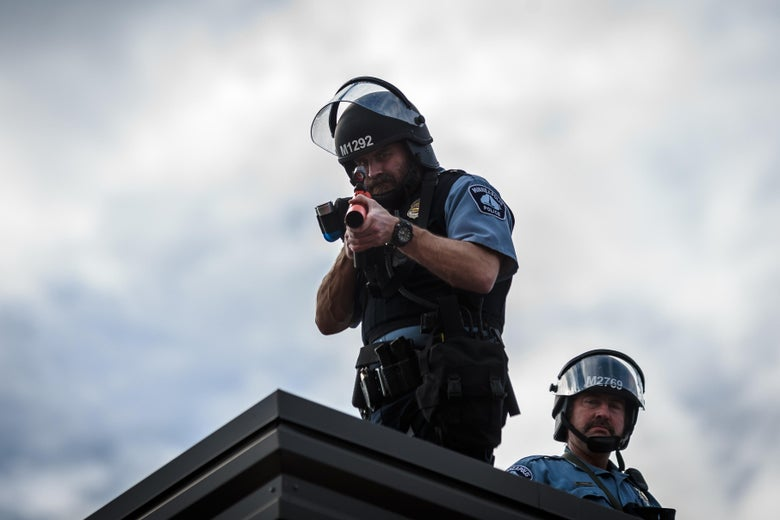 Two police officers stand on the roof, one aiming a weapon toward the camera.
