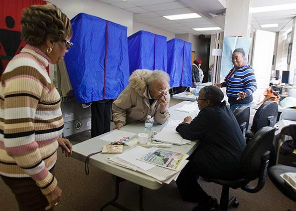 A voter signs in at her polling place inside the Concerned Black Men's office in November 2012 in North Philadelphia