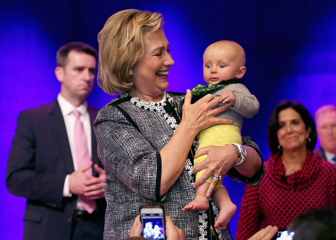 Former Secretary of State Hillary Clinton holds a baby