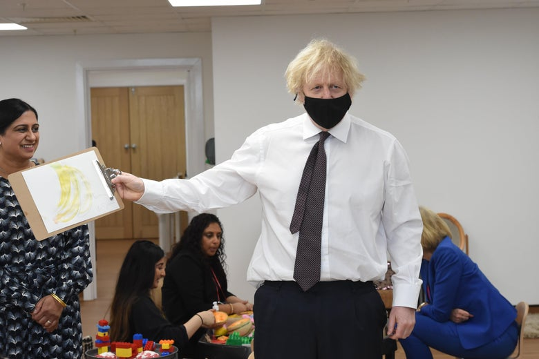 Boris Johnson stands in a classroom and holds up a clipboard with a drawing of a bunch of bananas.