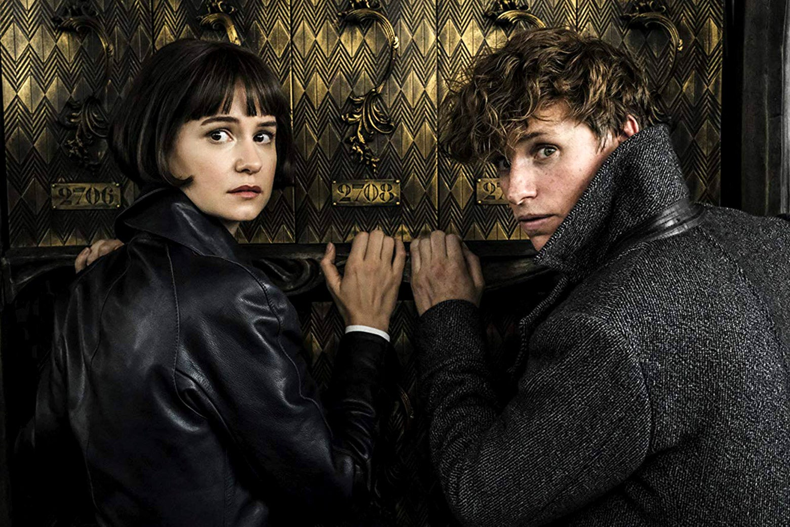 Katherine Waterston and Eddie Redmayne turn to look at the camera.