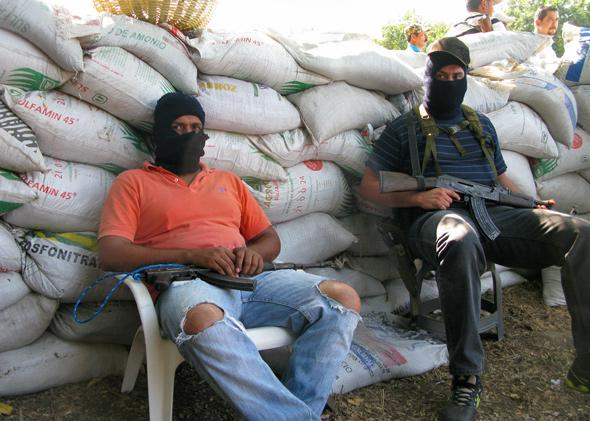 Vigilantes in fight against Knights Templar drug cartel at barricade on edge of Apatzingan, Mexico, Jan. 17, 2014