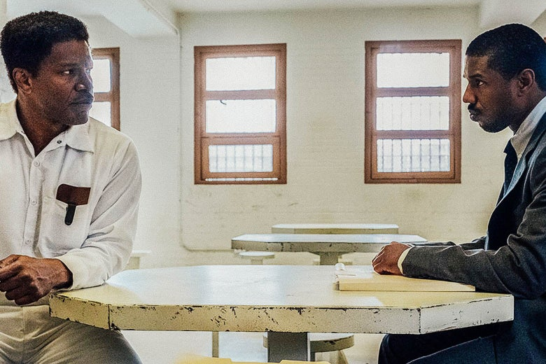 Jamie Foxx and Michael B. Jordan sit across a table from each other in a prison visitation room.