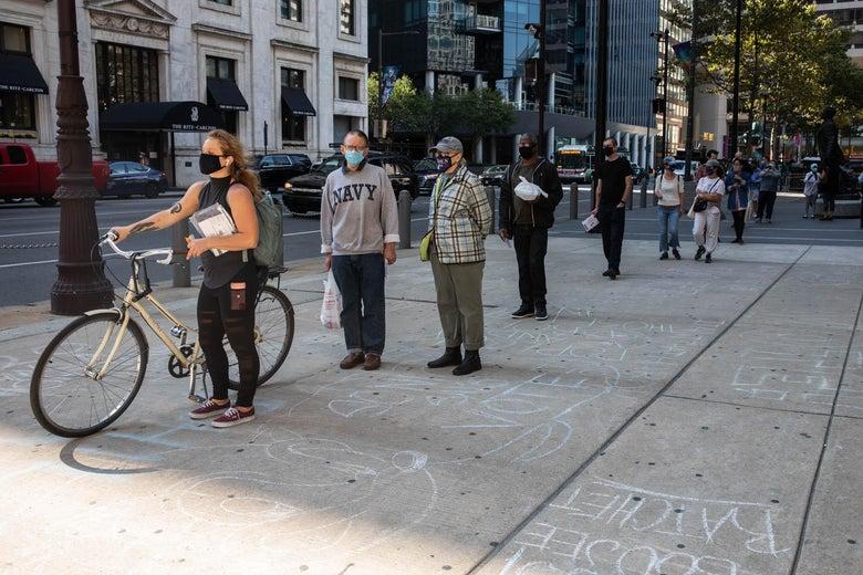 People wearing masks wait in a socially distanced line on the sidewalk