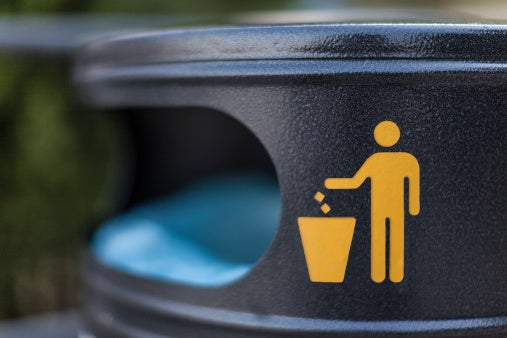 An outdoor garbage can with a graphic depicting a person throwing something in it.
