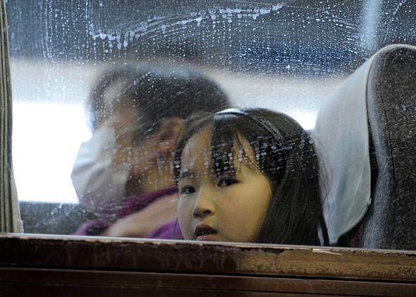 Girl aboard a bus evacuating from Yamagata