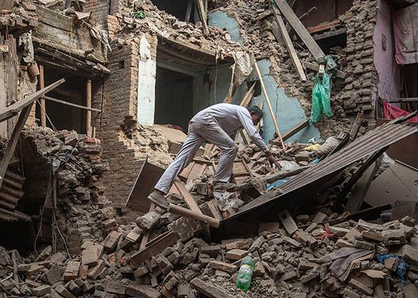 A man climbs on top of debris after buildings collapsed on April 26, 2015 in Bhaktapur, Nepal.