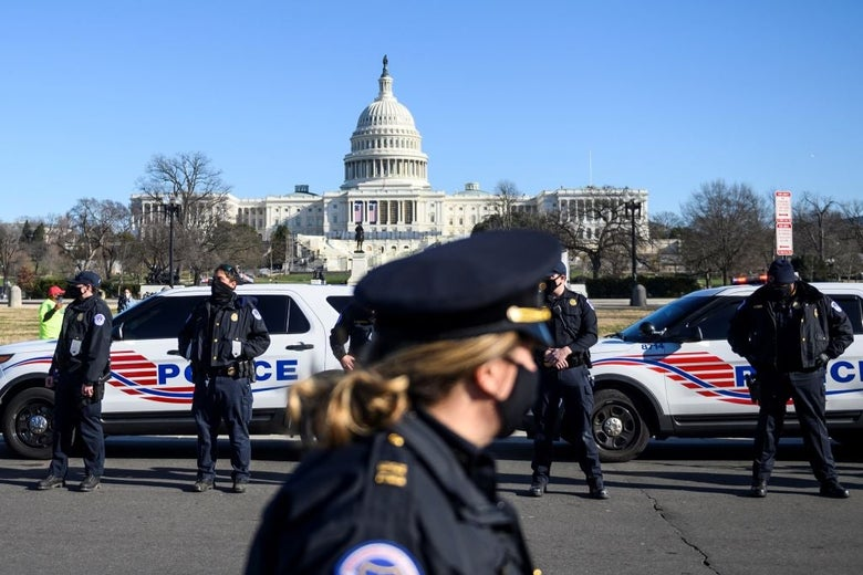 A police officer walks in the foreground; across a road from her four other officers stand in front of police cruisers. The Capitol dome is seen behind them in the distance.
