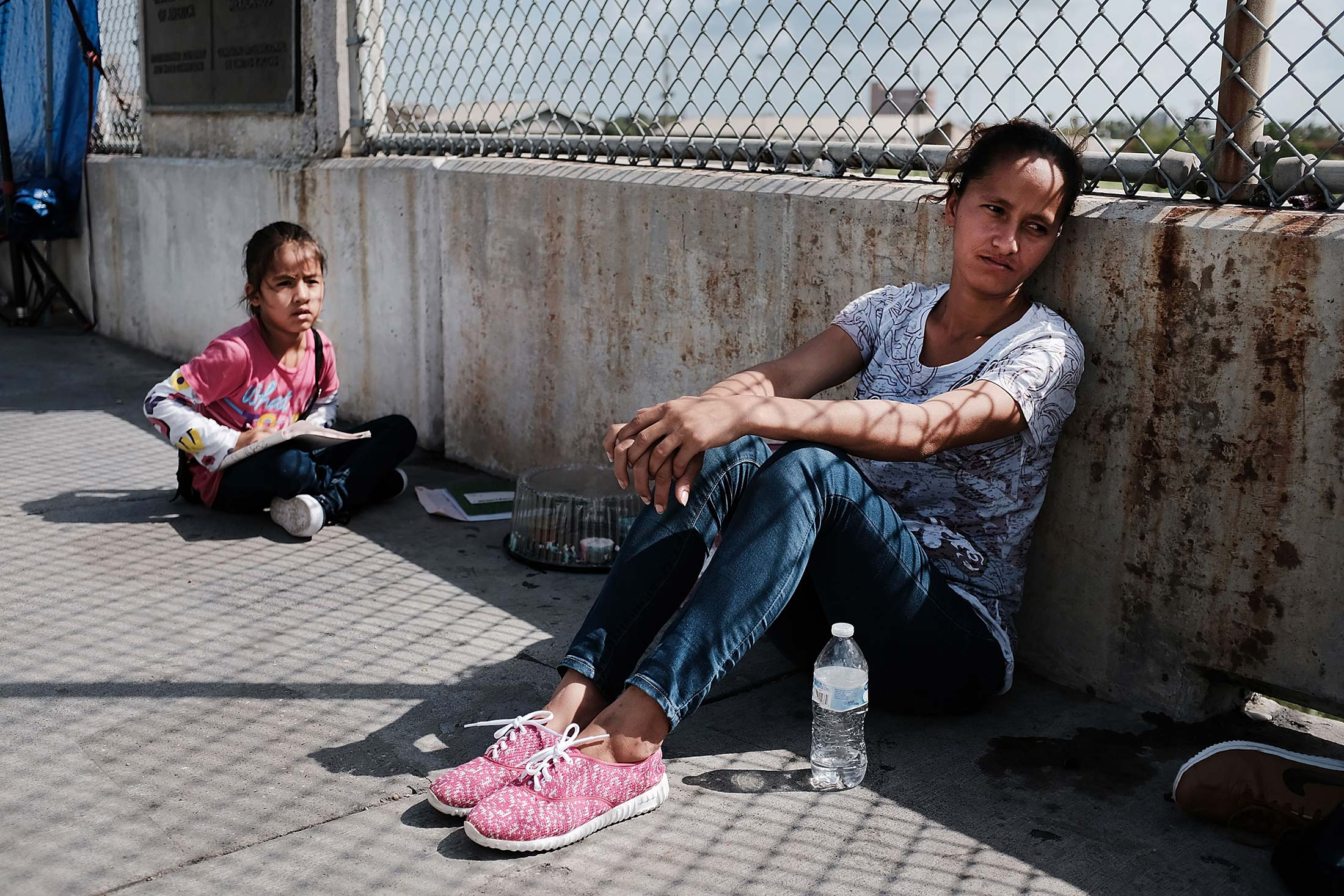 Migrant woman and child sitting on concrete bridge.