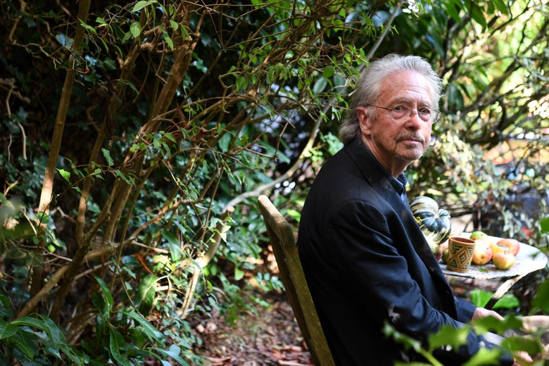 Peter Handke sits at a table with a mug and several apples against a backdrop of greenery.