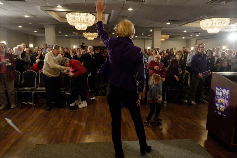 Elizabeth Warren seen from the back as she waves to a crowd of members of SEA/SEIU Local 1984, state employees, at the Holiday Inn in Concord, New Hampshire.