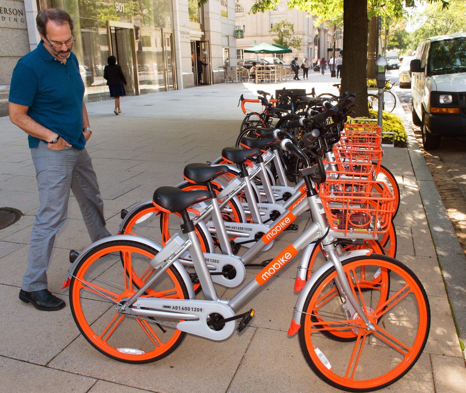 A man looks over Mobikes on the streets of Washington on Sept. 20.