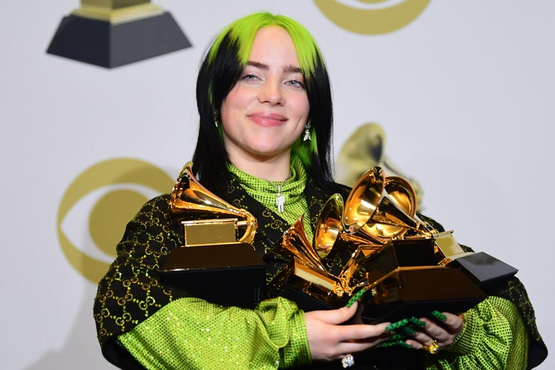 Billie Eilish carries an armful of Grammy trophies.