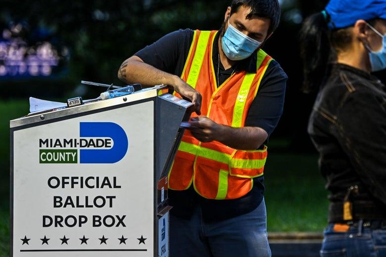 A man puts a ballot in a drop box