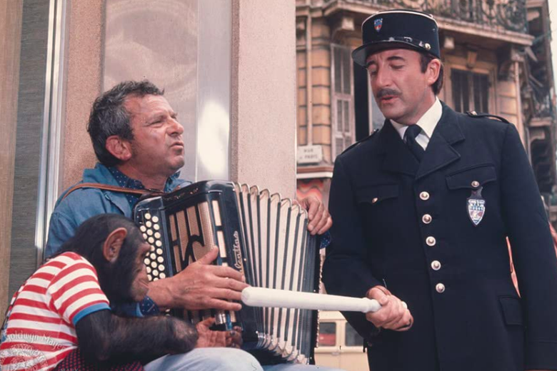 Peter Sellers, dressed in a police uniform, points a baton at a monkey wearing a striped shirt. John Bluthal plays an accordian.