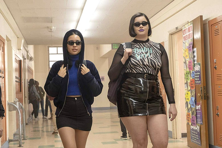 Two teen girls walk down a hallway in a school wearing sunglasses and black skirts.