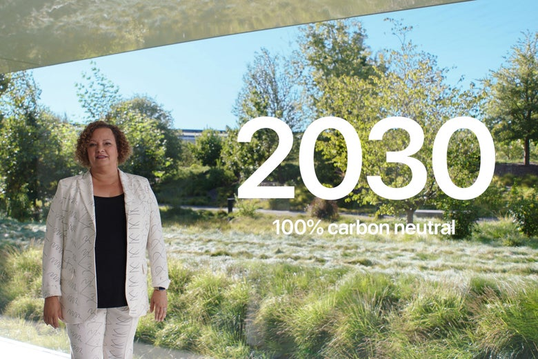 "A woman stands in front of a screen that displays a nature scene and the words ""2030 100% carbon neutral"""