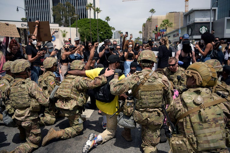 Camo-clad National Guardsmen kneel with protesters.