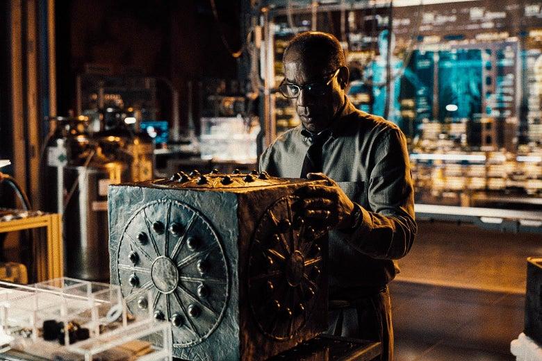 A man looks at a big black box.
