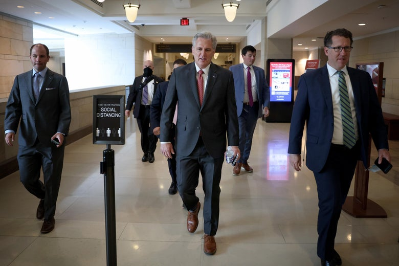 Kevin McCarthy leaves a meeting of the House Republican Conference, walking down a hallway with several men in suits around him