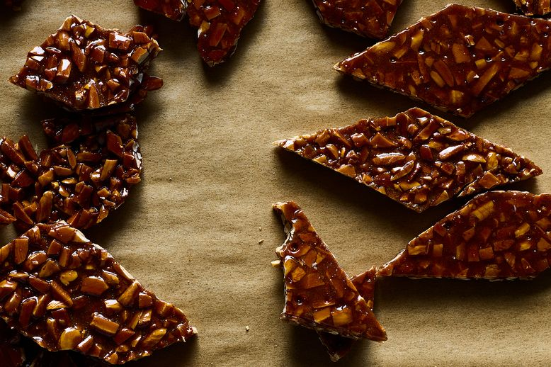 Pieces of almond brittle on parchment paper.