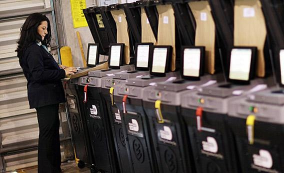 An election official goes through the steps to check voting machines for accuracy