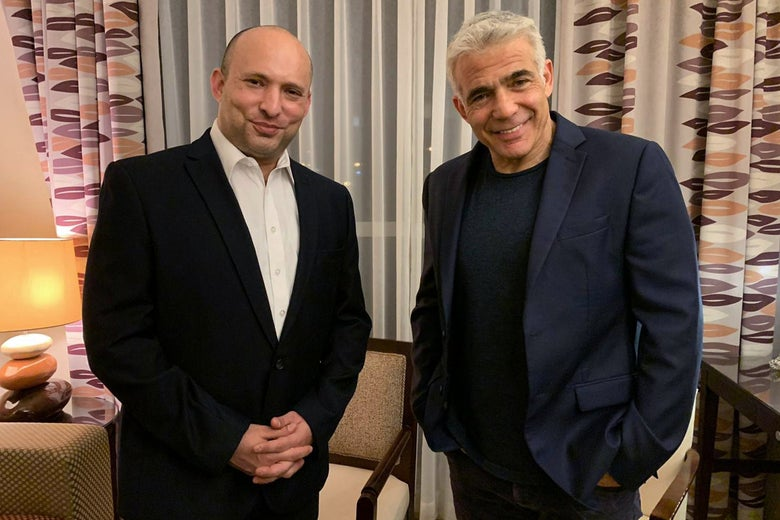 Bennett and Lapid standing in front of patterned curtains, smiling.