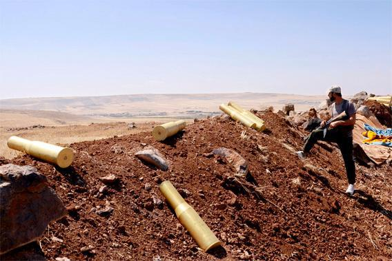 A man belonging to forces loyal to Syria's President Bashar al-Assad stands next to spent ammunition rounds in Tal El-Tineh village, during what they said was an operation to occupy it,  in the southern countryside of Aleppo, June 16, 2013.