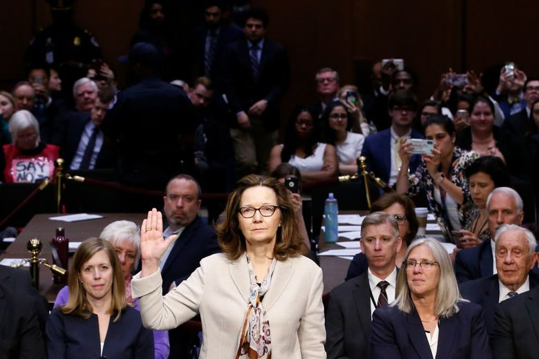 Gina Haspel raises her right hand to be sworn in in front of a crowded hearing room.