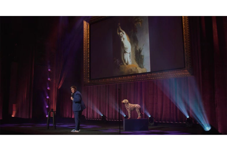 Hannah Gadsby on stage in front of a Rembrandt painting of Andromeda chained to her rock.