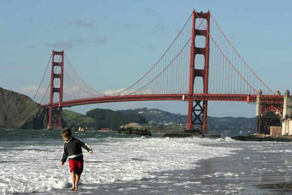 A boy plays in the water at Baker Beach near the Golden Gate Bridge March 25, 2005 in San Francisco, California.