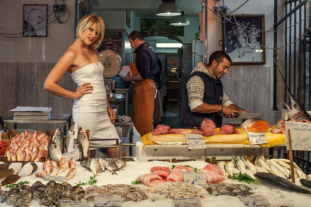 PALERMO, ITALY - OCTOBER 27 2013: an advertising photo shooting in the Vucciria Street Market. A blonde sexy woman is a timeless cliché that seems to work in every possible situation. At first I didn't notice it was a set up situation. It catched my attention, but it didn't seem impossible to be true. I never knew what was the shooting for.