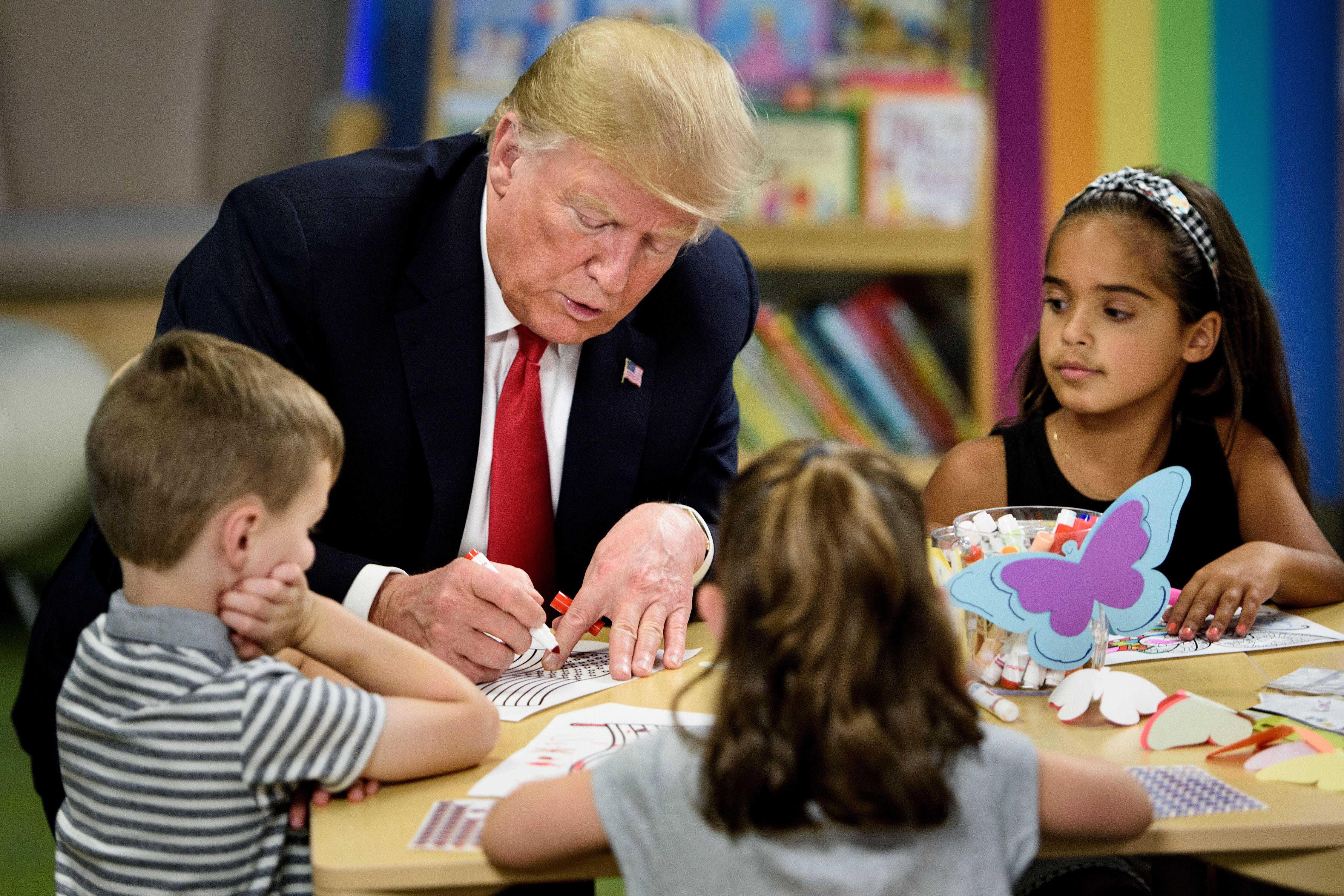 President Donald Trump colors in an American flag while children seated around him look on and color.
