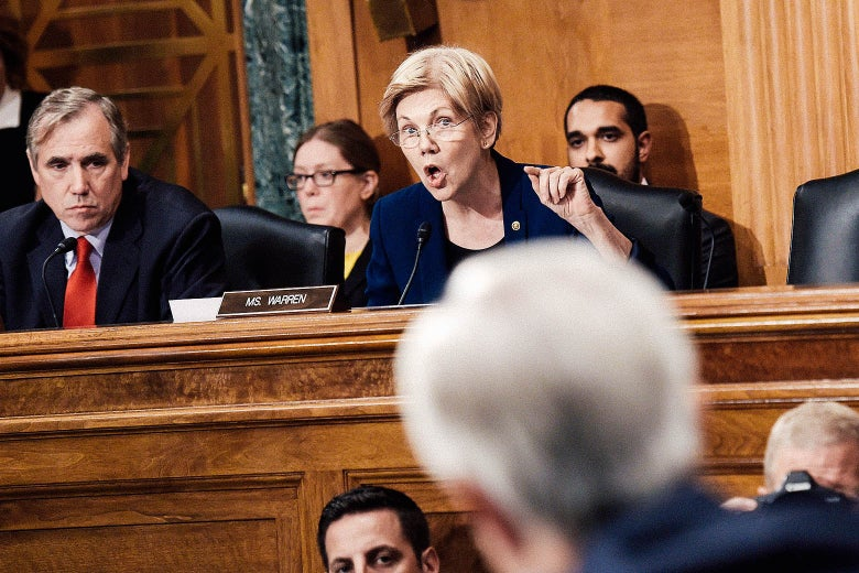 Elizabeth Warren, sitting at a panel while surrounded by others, speaks into a microphone.