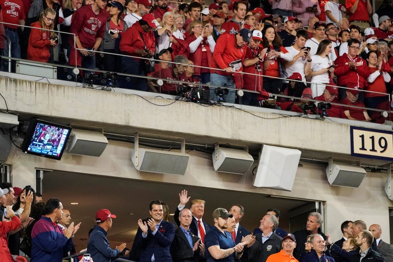 Trump waves from a luxury box above which fans can be seen in the upper deck.
