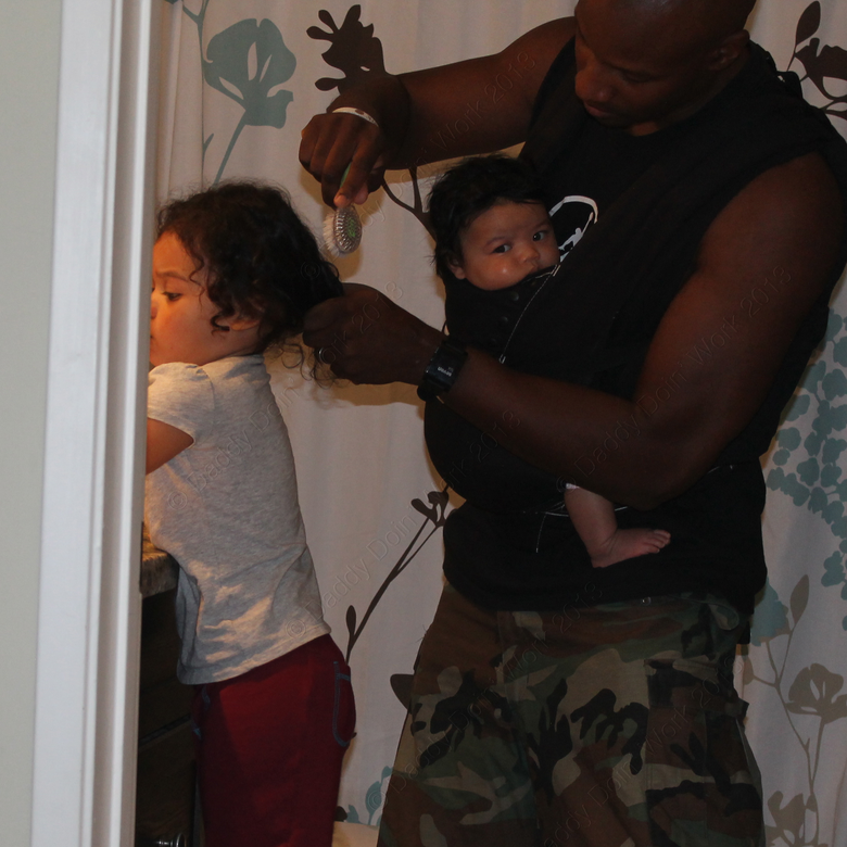 The author wearing his baby in a chest carrier while he brushes his older daughter's hair