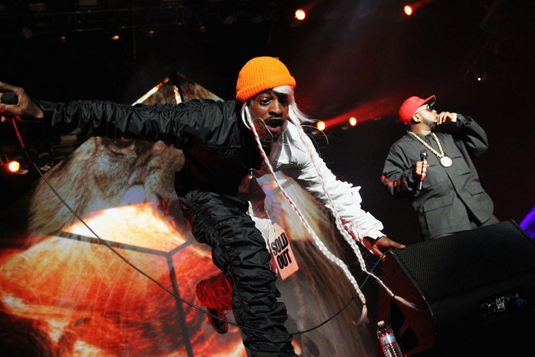 Two men in orange hats, black shirts, and black pants stand on a concert stage performing in front of red stage lights.