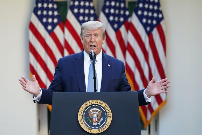 Trump raises both arms as he speaks at a podium during the daily coronavirus briefing.