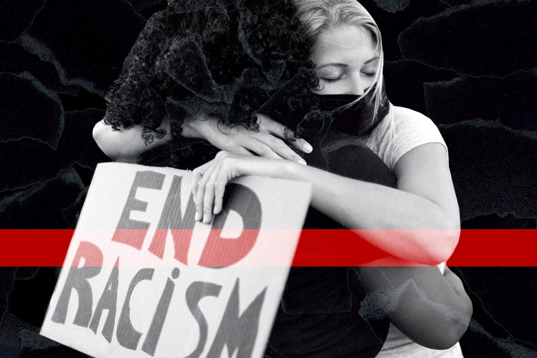 """A white woman with an """"End Racism"""" sign hugs a Black woman."""