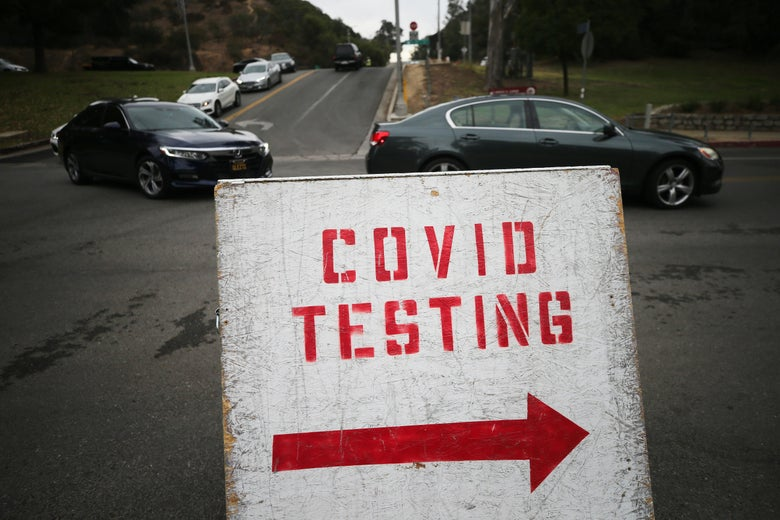 "Cars lined up to enter the COVID-19 testing site at Dodger Stadium in Los Angeles, with a sign marked ""COVID TESTING"" in the foreground"